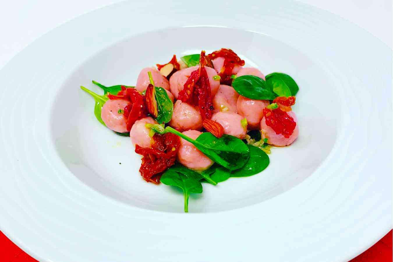 Gnocchi rosa di barbabietola, con spinacini e pomodorini secchi